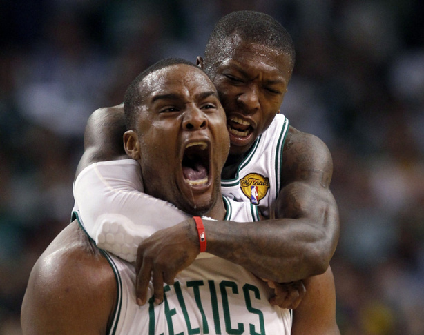 Boston Celtics guard Nate Robinson jumps on the back of Boston Celtics forward Glen Davis in Boston